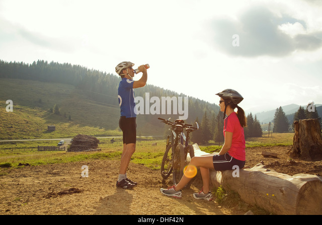 Man and woman resting with mountain bikes, Styria, Austria - Stock Image