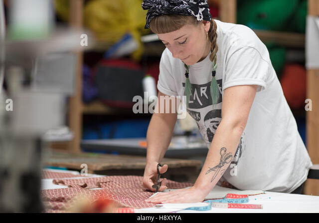 Young tattooed seamstress cutting out fabric - Stock-Bilder