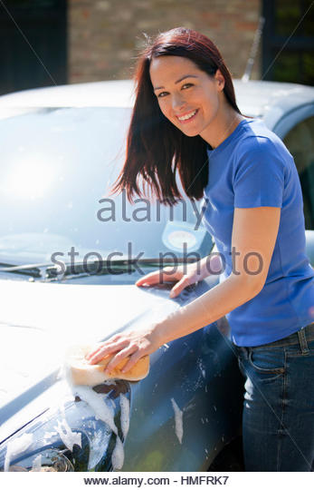 Portrait happy woman washing car with sponge in sunny summer driveway - Stock-Bilder