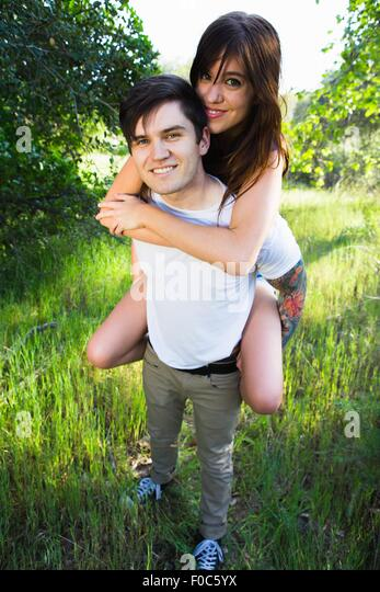 Young man giving girlfriend piggyback ride in park - Stock Image