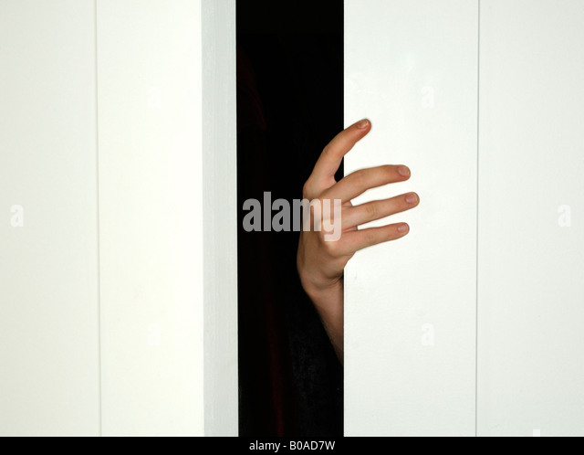 A hand holding open closed a white door - Stock Image