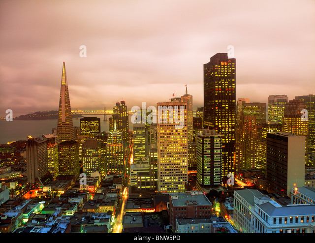 Office building lights with TransAmerica Pyramid and Oakland Bay Bridge in San Francisco skyline at dusk - Stock Image