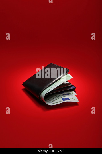 A black leather wallet filled with EU currency on a bright red background - Stock Image