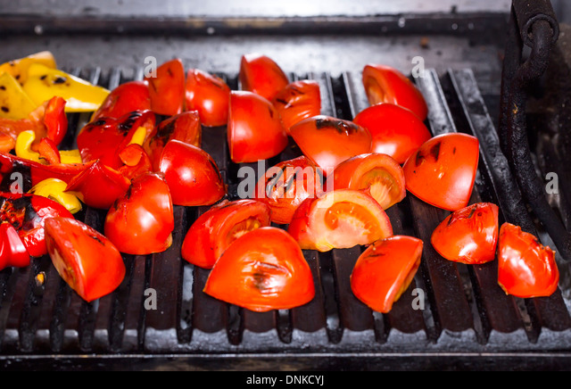 cooking vegetables on the grill in the kitchen at the restaurant - Stock Image