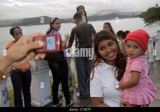 Panama City Panama Amador Panama Canal baby sister Hispanic girl toddler family take picture pose cell phone camera - Stock Image