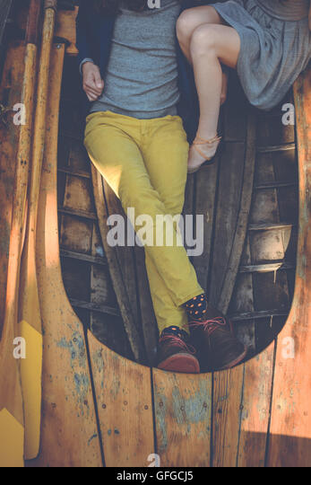 A well dressed man and woman sitting in a rowboat. Nautical fashion. Cropped onto lovely legs. - Stock Image