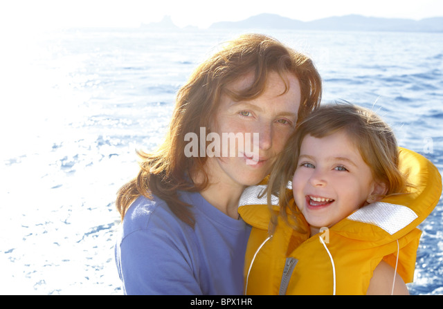 mother and daughter safety vest backlight sea smiling - Stock Image