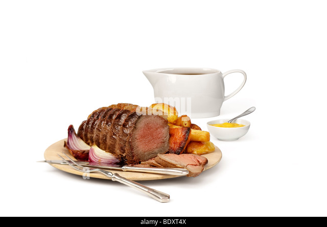 Roast beef on a carving board, with gravy boat and mustard pot. - Stock Image
