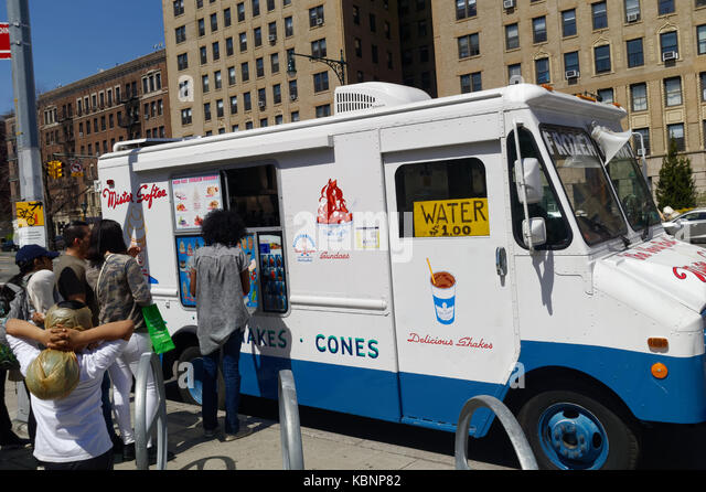 Adults and kids lining up to buy from an ice cream truck in Brooklyn, New York. - Stock Image