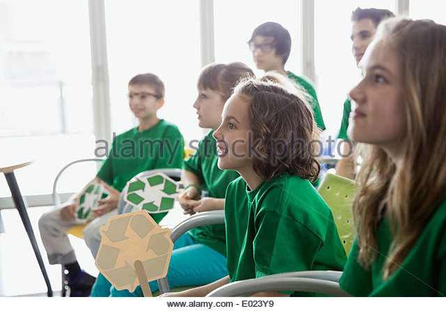 Elementary students with recycle signs in classroom - Stock Image