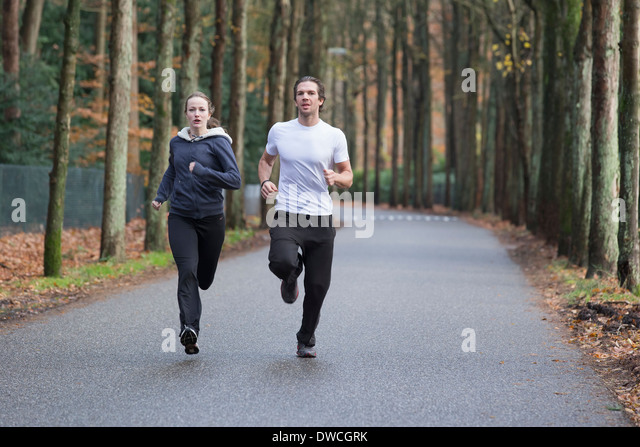 Couple running through forest - Stock-Bilder