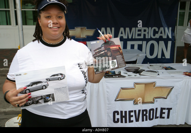 Florida Coconut Grove Grand Avenue Bahamas Goombay Festival Black woman taking survey Chevrolet car truck exhibit - Stock Image