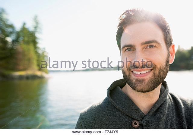 Portrait smiling brunette man beard at sunny lakeside - Stock-Bilder