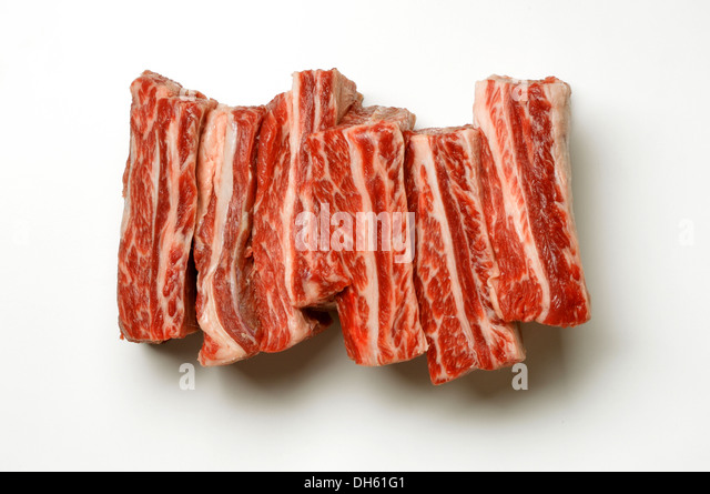 Uncooked beef short ribs on a white background. - Stock Image