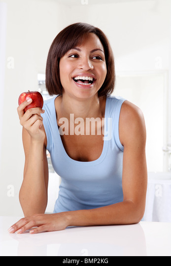 WOMAN HOLDING RED APPLE - Stock Image
