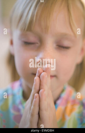 Girl praying with eyes closed - Stock-Bilder