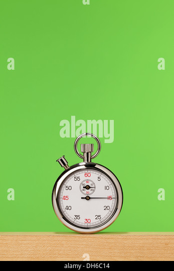 A stopwatch on a wooden shelf with a bright green background - Stock Image