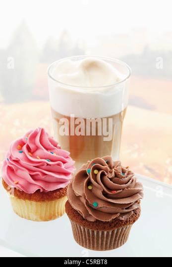 Close up of buttercream cupcakes with glass of latte macchiato - Stock-Bilder