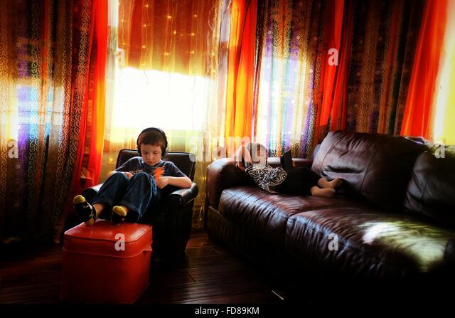 Siblings Relaxing At Home - Stock Image