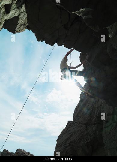 Rock climber scaling steep rock face - Stock-Bilder