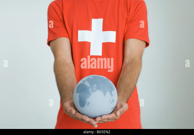 Man wearing Swiss flag tee-shirt, holding globe with both hands - Stock Image