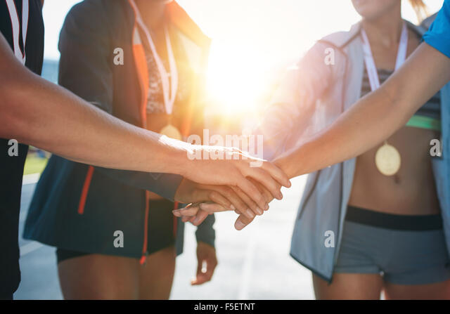 Sports people with hands together in huddle. Team with hands together celebrating success after winning athletics - Stock Image