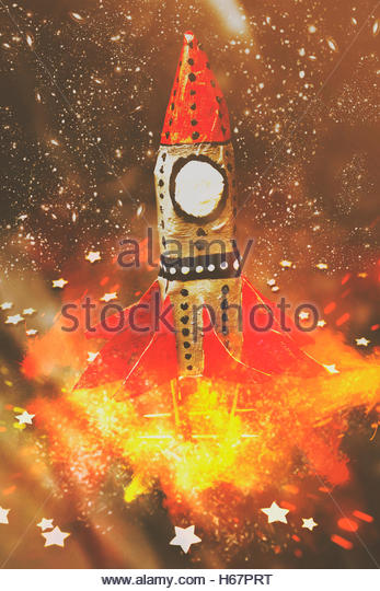 Handmade retro rocket launching into a stellar orbit of growth with fire thrusters flaming. Launch of early learning - Stock Image