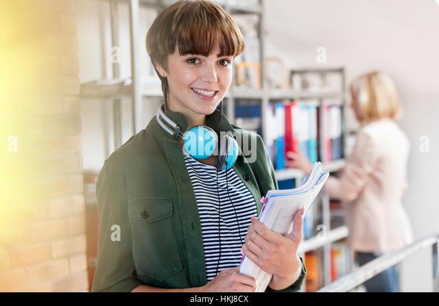 Portrait smiling female design professional with headphones holding paperwork in design library - Stock-Bilder