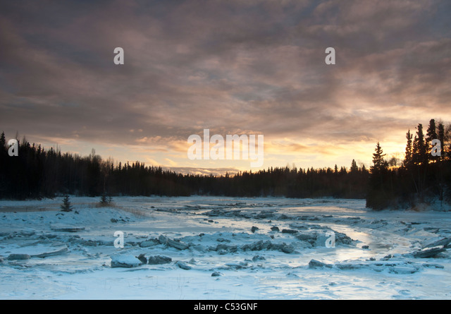 An ice-covered Fish Creek reflects the afternoon sky near the Tony Knowles Coastal Trail and Westchester Lagoon, - Stock Image