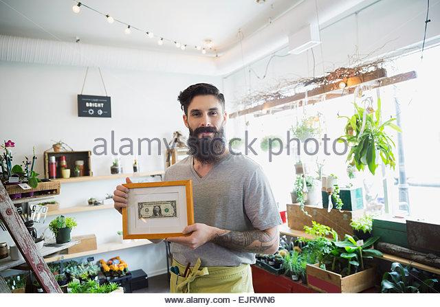 Portrait of terrarium shop owner showing first dollar - Stock Image