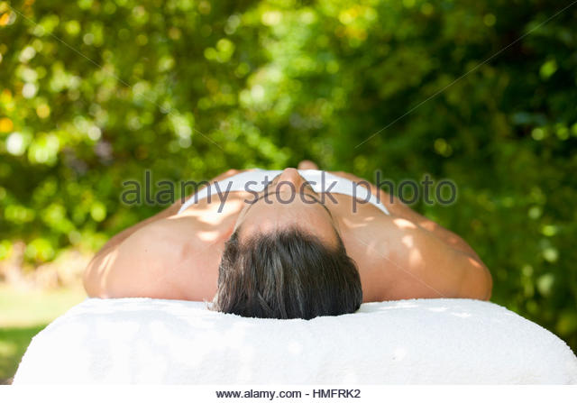 Serene man laying on massage table under tree - Stock-Bilder