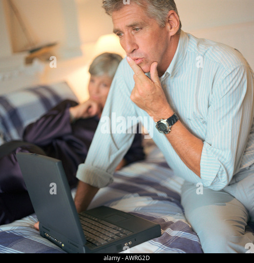 Mature man using laptop computer on bed, woman in background - Stock Image