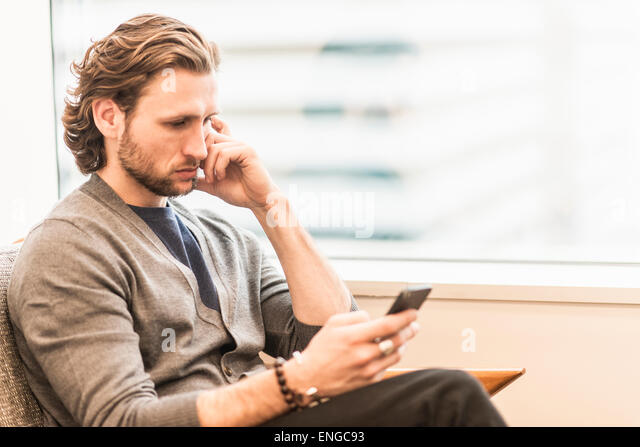 A bearded man sitting frowning and checking his phone. - Stock Image