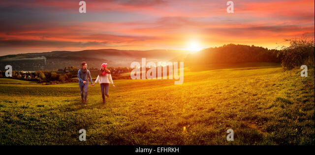 Loving couple holding hands running on the field. beautiful landscape - Stock-Bilder