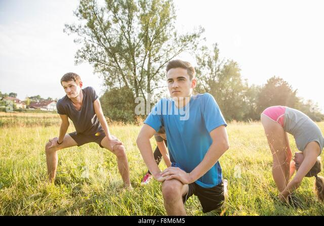 Group of friends exercising in field - Stock Image