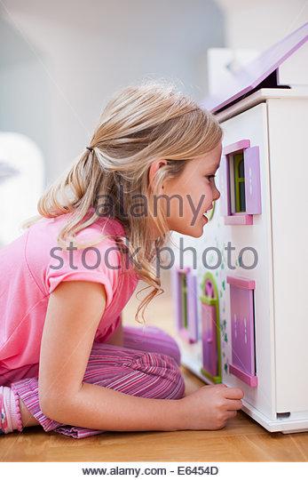Girl peering into dollhouse - Stock Image