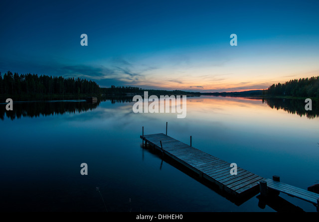 Lake and wooden pier at dawn, Skelleftea, Lapland, Sweden - Stock Image