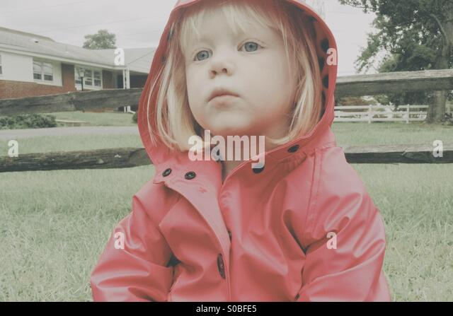 Young blond girl wearing a pink rain coat sitting on the ground. - Stock Image