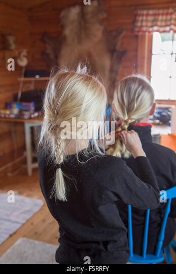 Norway, Girl (10-11) tying mother's hair - Stock Image