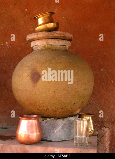 An earthen pot with metal glasses India Rajasthan - Stock Image