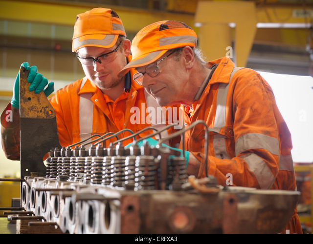 Engineer teaching apprentice in factory - Stock Image