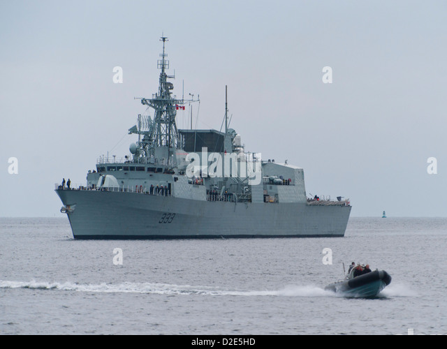 A rigid hulled inflatable boat (RHIB) passes in front of the Royal Canadian Navy frigate HMCS TORONTO (FFH 333). - Stock Image