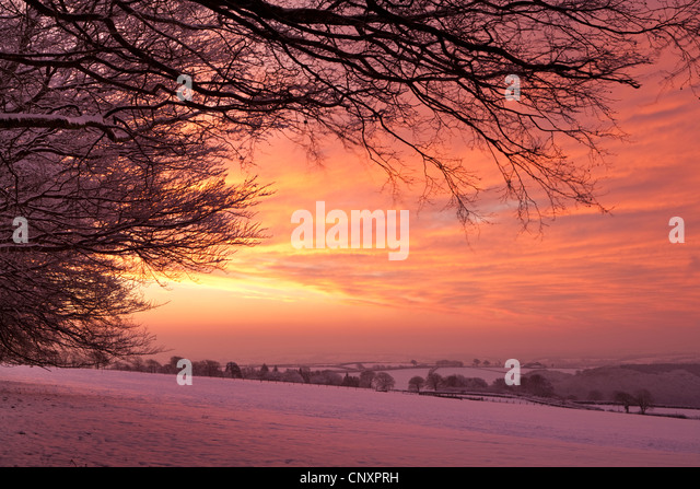 Spectacular dawn sky above snow covered countryside, Exmoor, Somerset, England. Winter (January) 2012. - Stock-Bilder