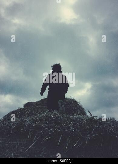 Little boy climbing a haystack - Stock Image