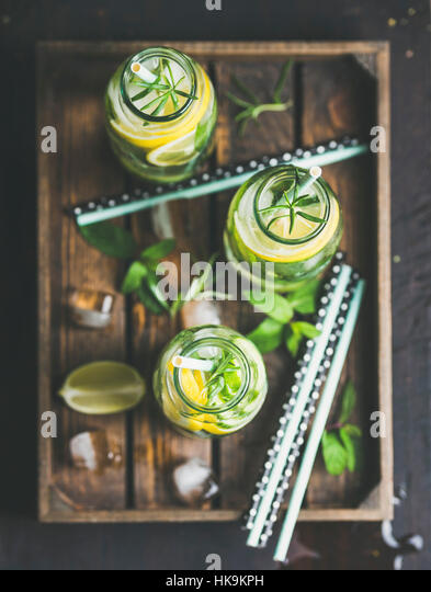 Citrus and herbs infused sassi water for detox, healthy eating, dieting in glass bottles in wooden tray over dark - Stock Image