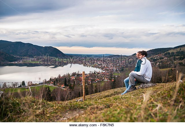 Side view of couple sitting looking at view of lake, Schliersee, Bavaria - Stock-Bilder