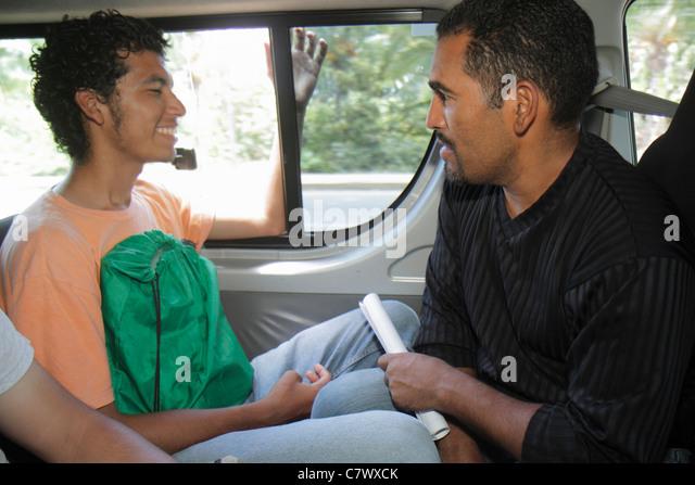 Nicaragua Managua bus to Granada microbus public transportation Hispanic man talking conversation young adult passenger - Stock Image