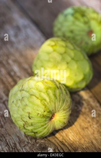 whole custard fruit on rustic wood board - Stock-Bilder