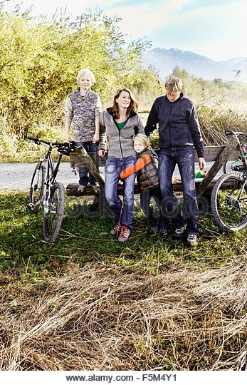 Family with bicycles leaning against bench by roadside - Stock Image