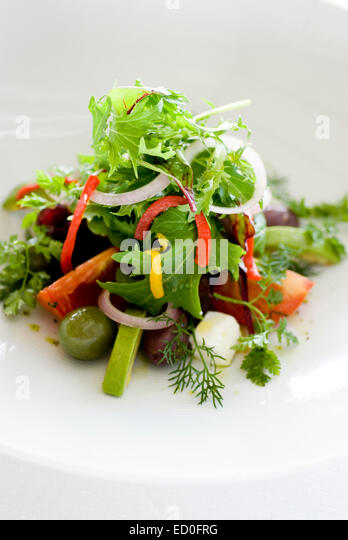 Fresh salad with vegetables and fruits on white plate - Stock Image